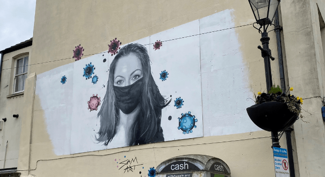 A drawing of a girl in a mask hangs in Rochester.