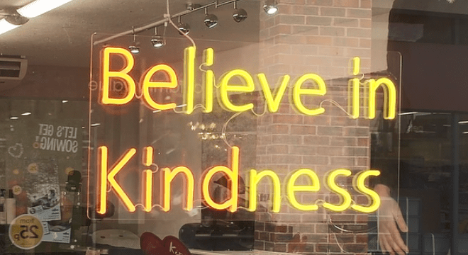 The words 'Believe in kindness' illuminate a shop window.
