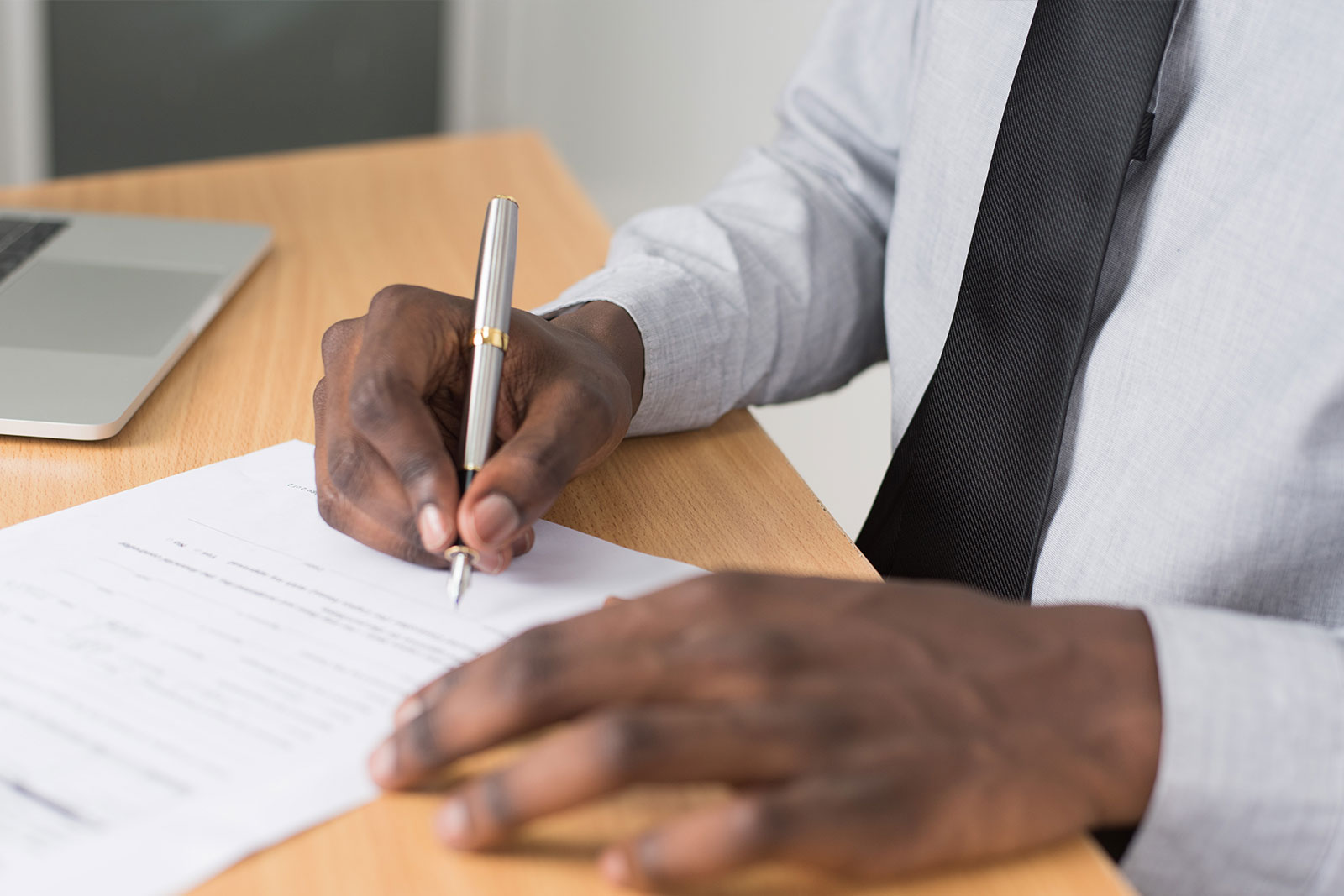 Professional man signing a document, image of hands only