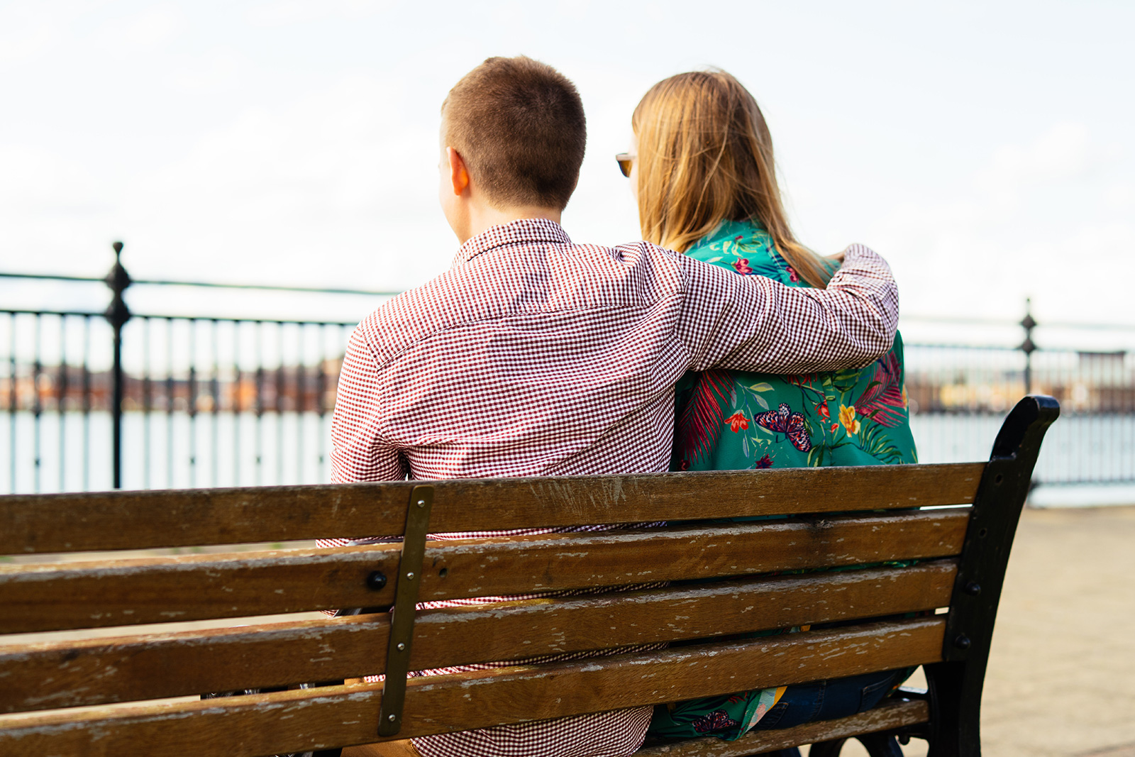 Couple sitting on bench facing a river