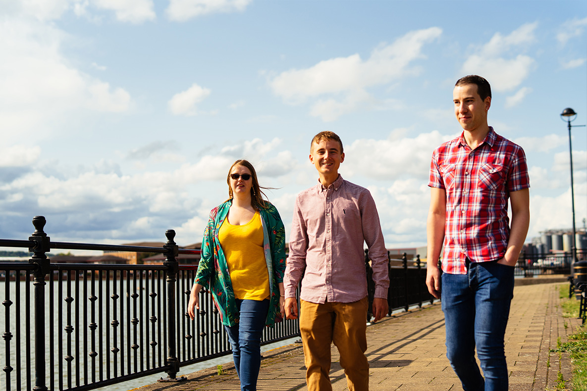 3 young people walking on a river path