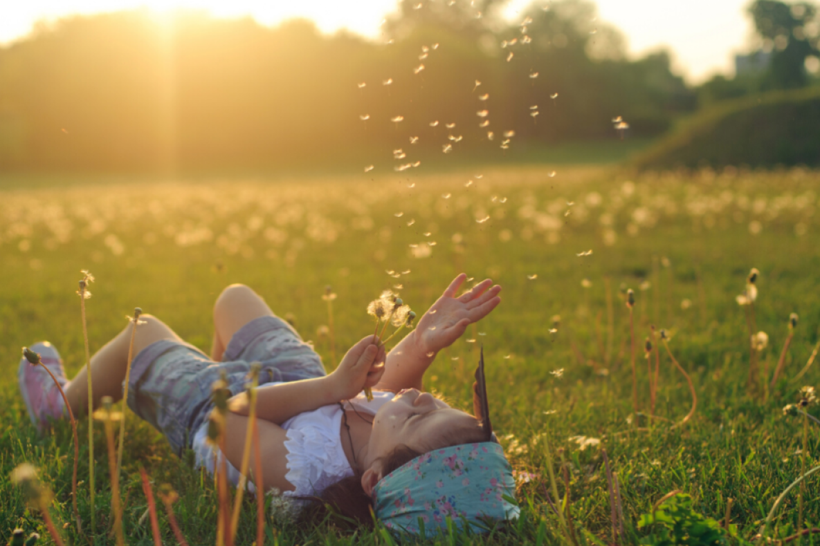 Child lying on back in a summer field making a wish